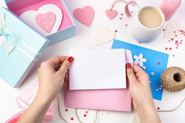 Une enveloppe et une feuille vierge blanche entre les mains d'une femme sur fond romantique dans des tons roses.