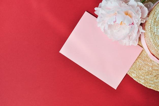 L'enveloppe et la fleur de pivoine rose à côté du chapeau de paille sur un rouge.