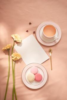 Enveloppe, fleurs et macarons avec tasse de thé