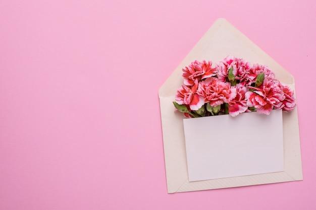 Une enveloppe avec des fleurs roses et une carte cadeau rose