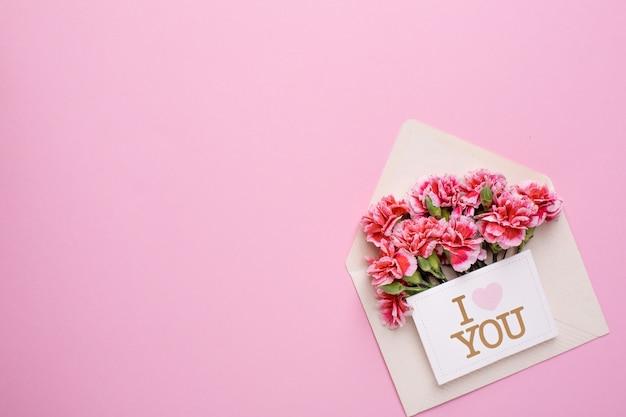 Une enveloppe avec des fleurs roses et une carte je t'aime sur rose