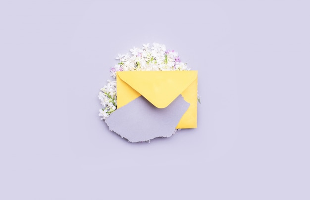 Enveloppe jaune pour une lettre avec des fleurs lilas. avec un morceau de papier déchiré pour le texte.