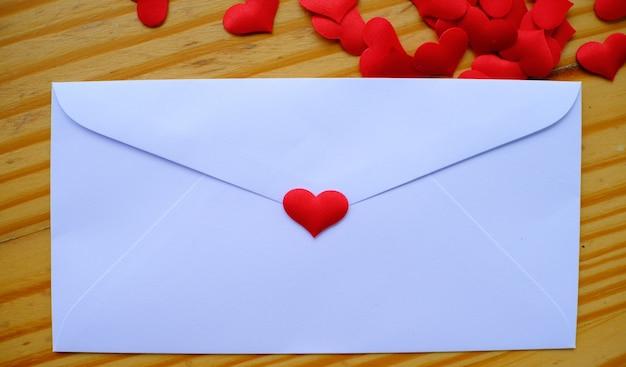 Enveloppe de lettre d'amour saint valentin avec coeurs sur fond en bois. copier l'espace.