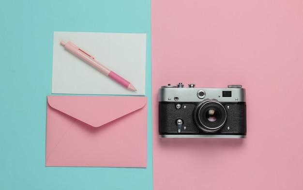 Enveloppe avec une lettre, appareil photo rétro sur fond pastel bleu rose. vue de dessus. concept de voyage
