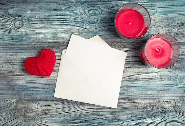 Une enveloppe avec une lettre blanche, deux bougies et un coeur rouge sur un fond en bois.