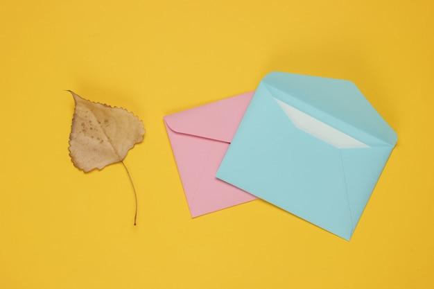 Enveloppe avec lettre, feuille d'automne sur fond jaune. lettre d'amour. vue de dessus