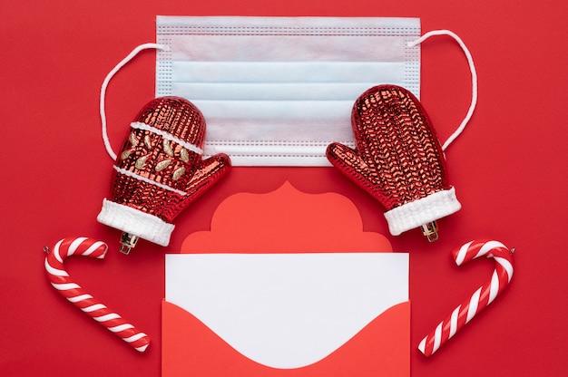 Enveloppe de lettre rouge de noël avec un espace pour le texte sur fond rouge ainsi qu'un masque médical comme symbole de sécurité