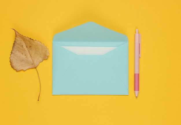 Enveloppe avec une lettre, un stylo, une feuille d'automne sur fond jaune. lettre d'amour.