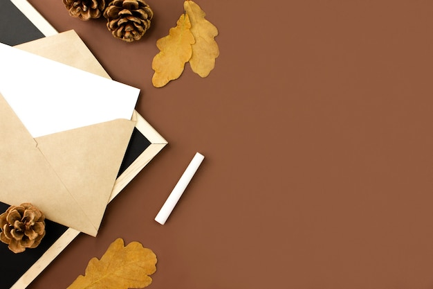 Enveloppe, lettre, tableau, cônes et feuilles orange sur fond marron, espace copie
