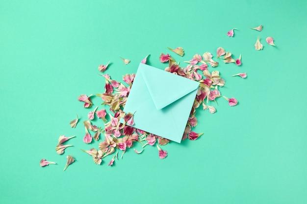 Enveloppe à la main avec des pétales de fleurs sur un fond turquoise clair et place pour le texte. mise à plat. carte de félicitations.