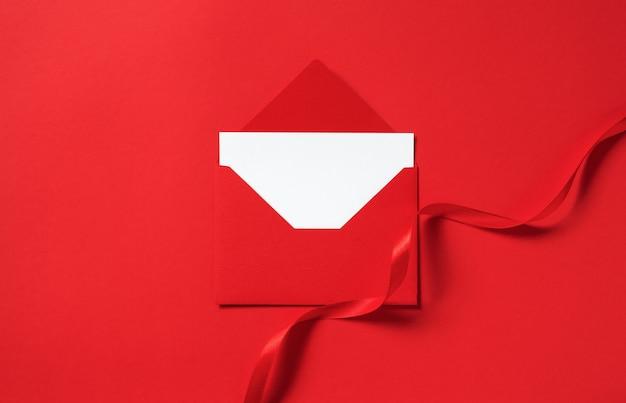 Enveloppe de maquette de vacances avec ruban atlas tourbillon sur rouge