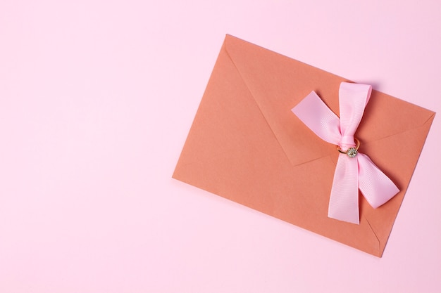 Une enveloppe avec un noeud rose sur fond rose pastel.