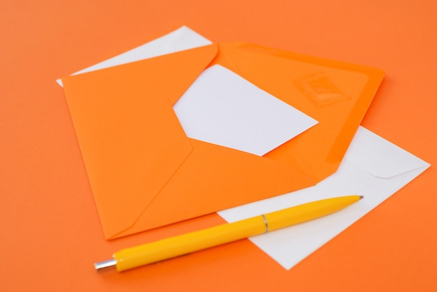 Enveloppe orange avec un stylo sur fond orange.