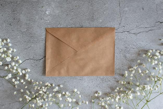 Enveloppe ouverte avec des arrangements de fleurs sur fond rose, vue de dessus. concept de voeux festif