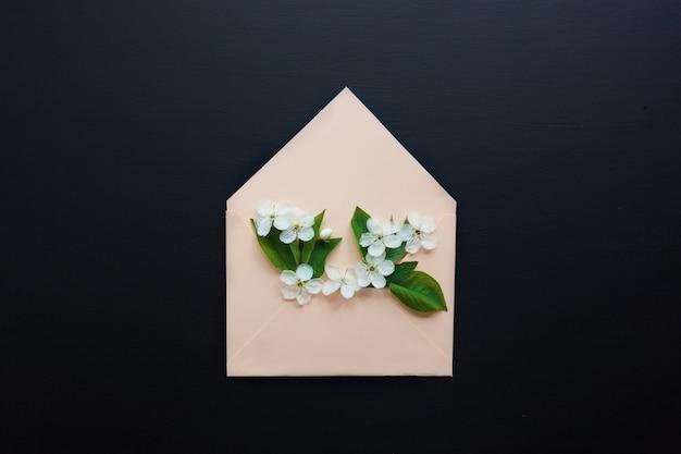Enveloppe ouverte avec des arrangements de fleurs de printemps sur fond noir