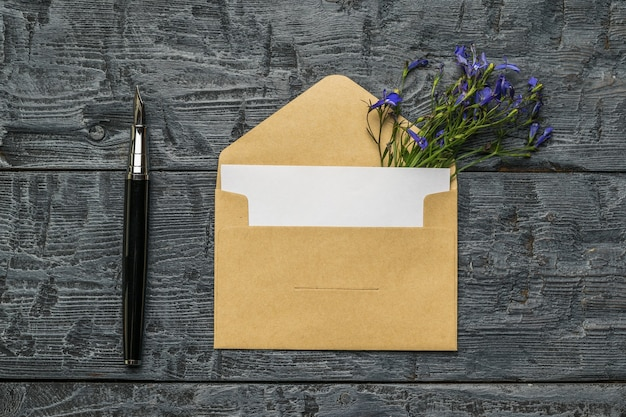 Une enveloppe ouverte avec une feuille de papier blanche, un stylo plume et des fleurs sur un fond en bois. mise à plat.