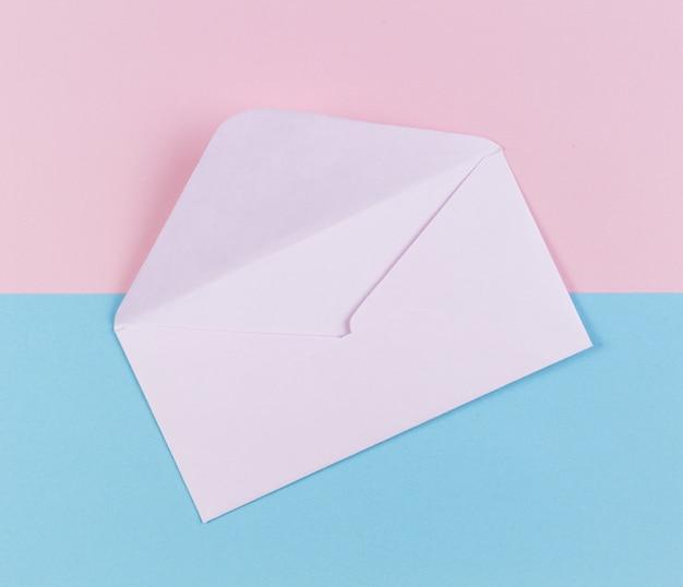 Une enveloppe ouverte sur fond rose et bleu pastel