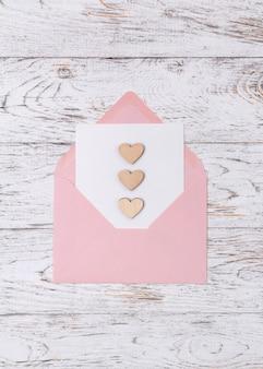 Enveloppe ouverte avec lettre et coeurs en bois sur table en bois blanc