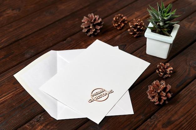 Enveloppe ouverte avec en-tête vierge sur fond de bois avec pommes de pin et petite plante dans un pot