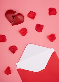 Enveloppe ouverte avec vide, coeur brisé et pétales de rose sur fond rose
