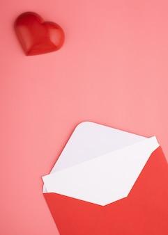 Enveloppe ouverte avec vide, coeur sur fond rose
