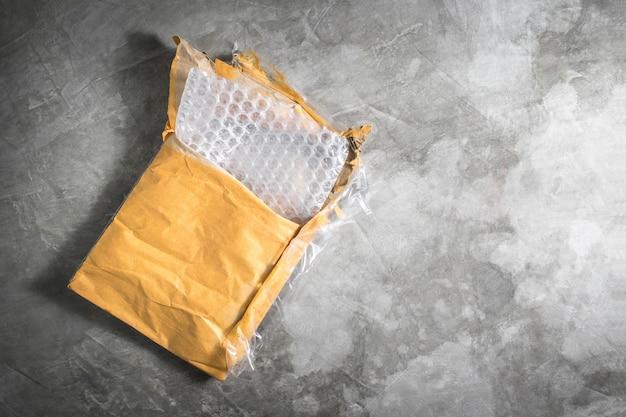 Enveloppe ouverte vintage avec film à bulles sur fond de carton de ciment.