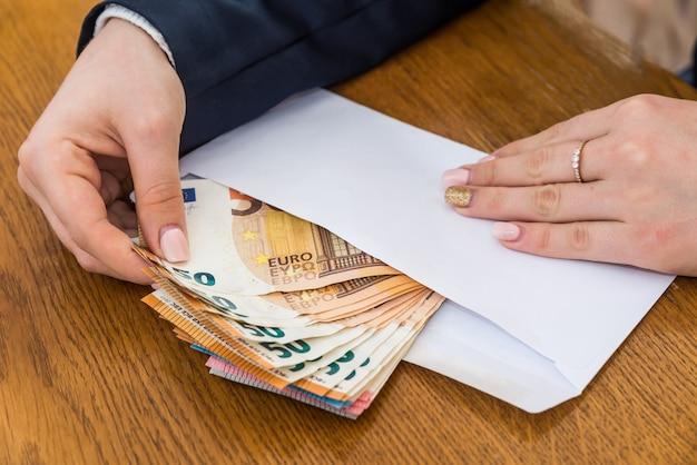 Enveloppe d'ouverture des mains féminines avec des billets en euros