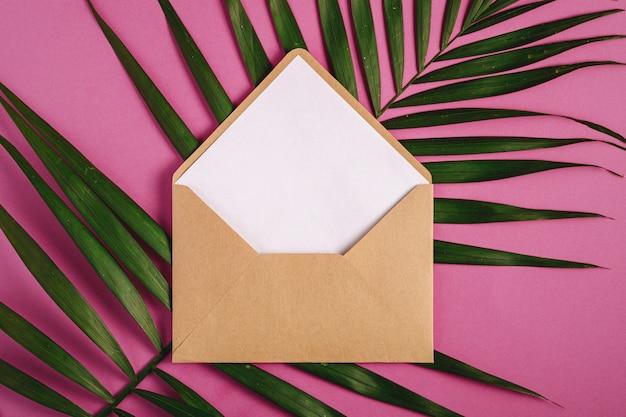 Enveloppe en papier brun kraft avec une carte vide blanche sur les feuilles de palmier, fond violet rose, lettre vierge maquette