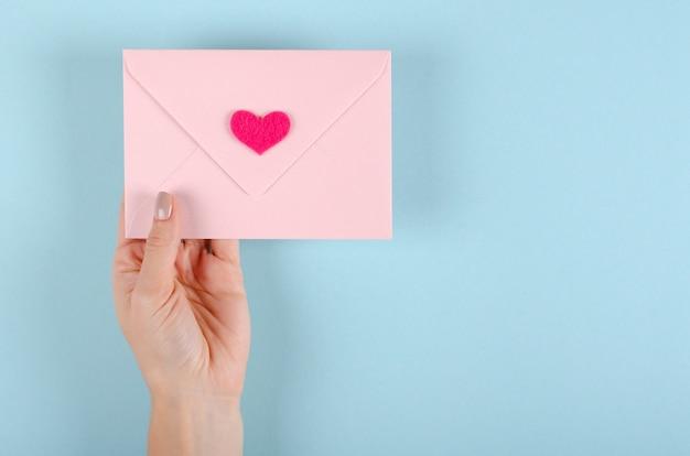 Enveloppe de papier avec composition coeur rouge sur fond bleu.