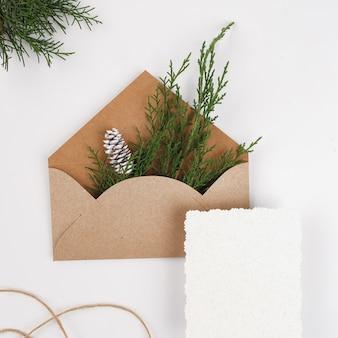 Enveloppe en papier craft avec des branches de sapin et du papier blanc