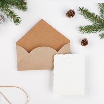 Enveloppe en papier craft avec des branches de sapin, des pommes de pin et du papier blanc