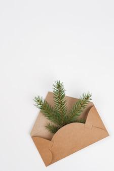 Enveloppe en papier craft avec des branches de sapin