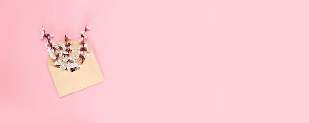 Enveloppe en papier craft ouverte pleine de fleurs de fleurs de printemps sur fond rose.