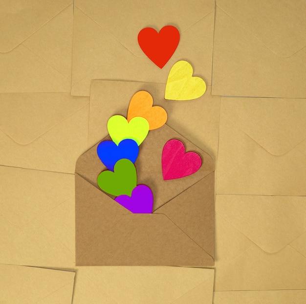 Enveloppe de papier kraft brun avec divers coeurs colorés arc-en-ciel sur brun uni