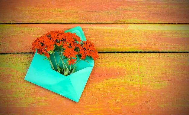Enveloppe en papier vert avec des fleurs de lychnis rouges de jardin frais sur fond de planches de bois vieilli. modèle floral festif. conception de carte de voeux. vue de dessus.
