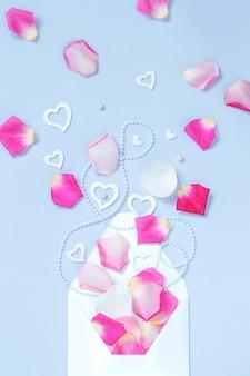 Enveloppe avec pétales et coeurs sur fond pastel