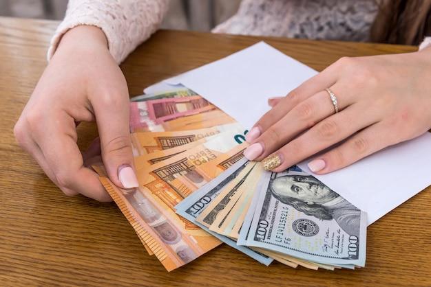 Enveloppe pleine d'euro et de dollar avec des mains féminines