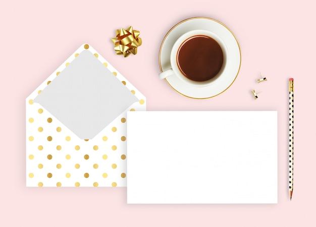 Enveloppe polka doré, tasse à café et crayon.