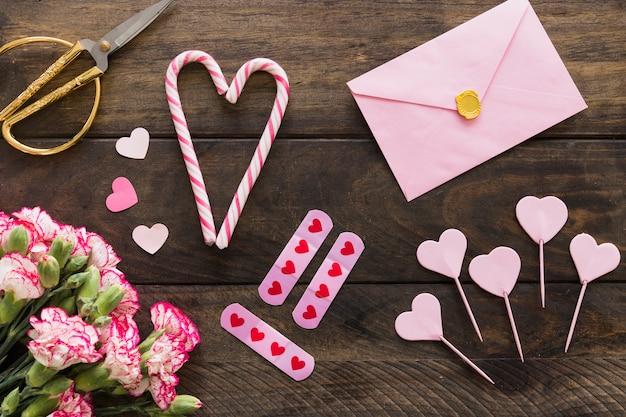 Enveloppe près de bouquet de fleurs, ciseaux et cannes de bonbon