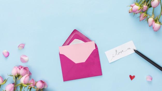 Enveloppe près du stylo, étiquette avec titre et fleurs