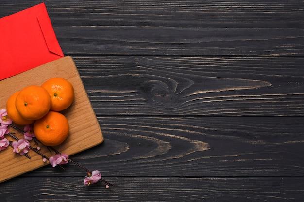 Enveloppe près des mandarines et branche à bord