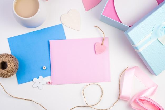 Enveloppe rose et bleue, coffret cadeau, café au lait et coeurs sur fond clair.