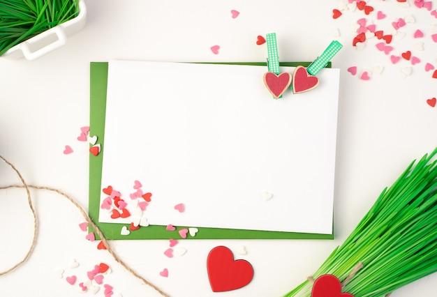 Enveloppe rose, bouquet vert et coeurs sur fond clair.
