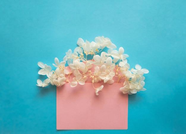 Enveloppe rose avec hortensia de fleurs blanches à l'intérieur sur fond bleu. modèle pour les newsletters et autres conceptions de courrier.