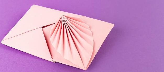 Enveloppe rose isolée sur fond violet, espace copie