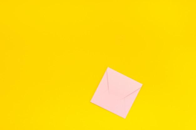 Enveloppe rose pastel sur fond jaune