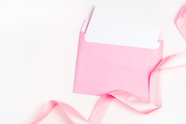 Enveloppe rose et ruban de satin sur fond clair.