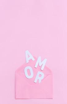 Enveloppe rose et texte amor sur un rose clair