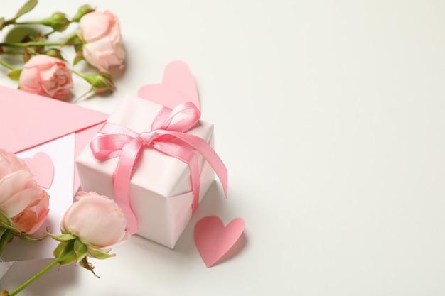 Enveloppe, roses, coeurs et boîte-cadeau sur fond blanc