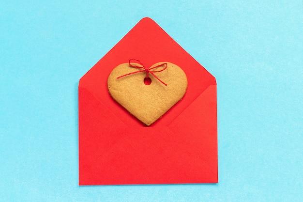 Enveloppe rouge et biscuits au gingembre en forme de coeur sur fond bleu